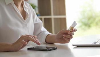 Mujer joven con tarjeta de crédito y uso de teléfonos inteligentes para compras en línea concepto de compras de pago en línea foto