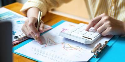 Mujer de negocios con calculadora y computadora portátil para hacer finanzas matemáticas en un escritorio de madera en la oficina y antecedentes de trabajo empresarial estadísticas de contabilidad fiscal y concepto de investigación analítica foto