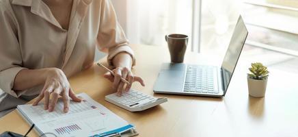 Mujer de negocios que trabaja en finanzas y contabilidad analizar el presupuesto financiero con calculadora y computadora portátil en la oficina foto