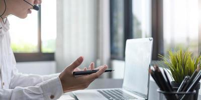 Gerente de joven empresario enfocado usando auriculares con micrófono involucrado en una reunión en línea distante con colegas o socios discutiendo problemas de trabajo utilizando la aplicación de computadora de videollamada foto
