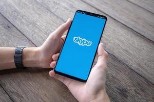chiang mai, tailandia, 11 de mayo de 2019, mano de hombre sosteniendo oneplus 6 con pantalla de inicio de sesión de la aplicación skype foto