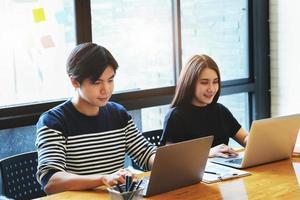 Empleados masculinos y femeninos que trabajan con ordenador portátil. foto