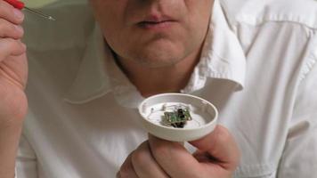 um homem de óculos examina um microcircuito video