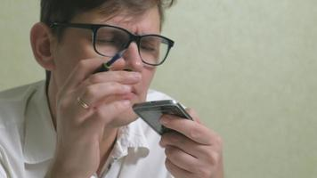 um homem de óculos examina um telefone antigo com uma tela de toque quebrada video