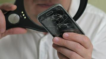 um homem de óculos examina um telefone antigo com uma tela de toque quebrada através de uma lupa video