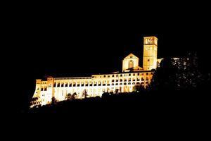 Vista de la basílica de Asís iluminada por la noche foto