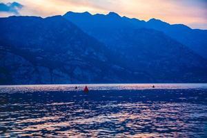 luces y sombras de la puesta de sol sobre el lago de garda foto