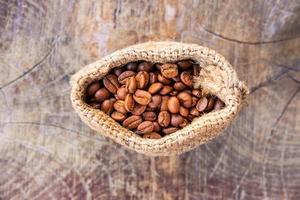 granos de café tostados en una bolsa de saco marrón foto