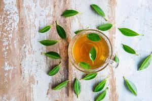 Taza de té y hojas de té frescas sobre una mesa de madera foto