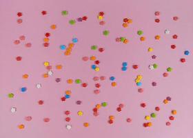 Coloridas flores de confeti dulce sobre fondo rosa foto