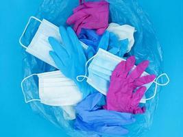Máscaras faciales de desechos de coronavirus pandémico médico y guantes de látex en una bolsa de basura sobre fondo azul foto