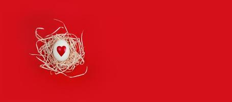 White egg with heart shape in decorative nest on red background with copy space photo