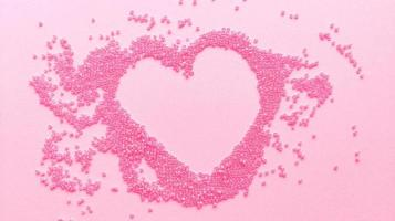 Hand made pink heart of beads on pastel texture background Flat lay with copy space Stock photo