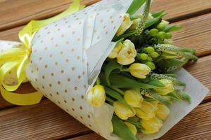 ramo de tulipanes amarillos en paquete blanco y tira foto