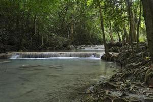 Beautiful waterfalls of turquoise water in the middle of the jungle in Thailand photo