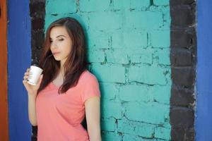 Smiling girl with brown hair near colorful wall photo