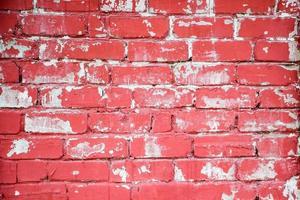 Pared de ladrillo rojo con pintura descascarada foto