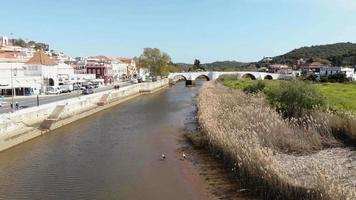 Fly over river on quiet sunny day. Quaint view of Silves, Algarve, Portugal video
