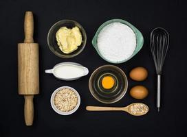 Herramientas e ingredientes para la masa sobre fondo negro foto