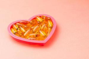 Cápsulas de aceite de pescado en el marco en forma de corazón sobre fondo rosa con espacio de copia foto