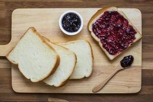Vista superior de rebanadas de pan casero con mermelada de grosella negra sobre la plancha de madera foto