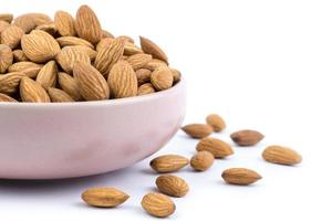 close up of Almonds in pink porcelain bowl on white background photo