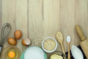 Top view with copy space of tools and ingredients for baking cake on wooden background photo