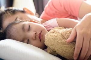 Close up cute asian baby girl and her mother Sleeping on the bed photo
