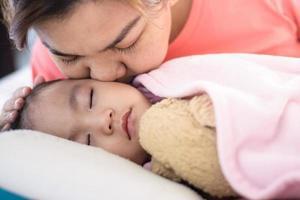 Cerrar madre asiática besando a su niña durmiendo en la cama foto