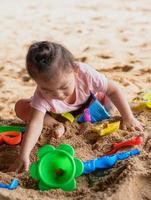 Cute asian baby girl playing with beach toys on the beach photo