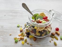 Frasco de vidrio con diversos frutos secos y nueces. foto