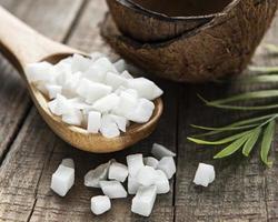 cubos de coco dulce seco en cuchara foto