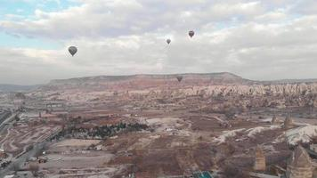 Hot air balloons fly over Goreme Valley in Cappadocia, Turkey - Ascending Wide Aerial video