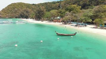 Touristic Banana Beach in Koh Hey, Coral Island, with Long-tail fishing boat moored near emerald shore, Thailand - Aerial Low angle Fly-backwards shot video