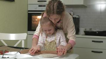 mujer e hija pequeña en la cocina de casa extendiendo la masa de pizza video