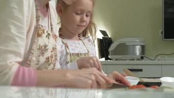 Woman and little daughter at home kitchen cutting vegetables for pizza video