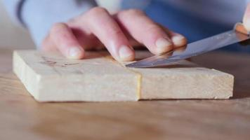 cutting off excess dried glue on a wooden board with a knife video
