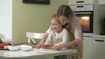 A woman and her little daughter are preparing pizza in the home kitchen video