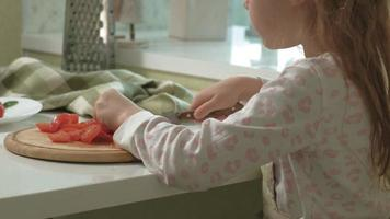 Little girl at home kitchen cutting vegetables for pizza video