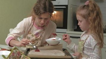 uma mulher e sua filha preparando pizza na cozinha de casa video