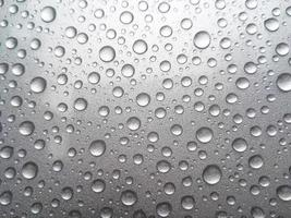Gota de rocío de lluvia sobre un fondo de color gris foto