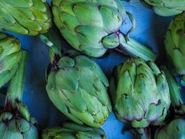 Alcachofas verdes dispuestas sobre un fondo azul. foto