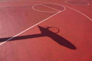 sombras de aro en la cancha de baloncesto de la calle foto