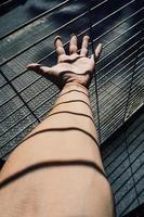 mano alcanzando una valla metálica foto