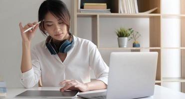 Mujer sentada ues portátil pensando en la solución del problema pensativa empleada reflexionando considerando la idea mirando la pantalla de la computadora tomando decisiones foto