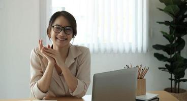 Portrait of smiling businesswoman sitting at desk in the office working on laptop photo