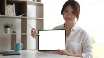 Close up view of female worker showing mock up tablet screen while standing in office room photo
