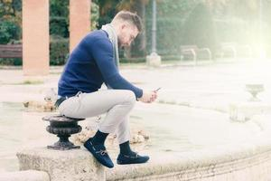 young man sitting in the fountain of a park looking at his cell phone photo