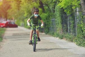 Happy kid having fun near home with a bicycle on beautiful spring day wearing protection mask for coronavirus Covid19 pandemic virus photo