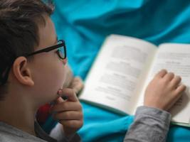 Little child 8 years old boy reading a book at home with his toy teddy bear photo